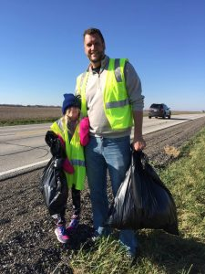 Rotarian and his daughter help pick-up along highway.